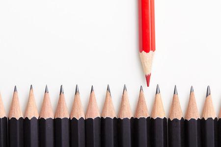 Foto de Red pencil standing out from crowd of plenty identical black fellows on white table.  - Imagen libre de derechos