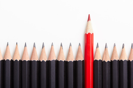 Foto per Red pencil standing out from crowd of plenty identical black fellows on white table.  - Immagine Royalty Free