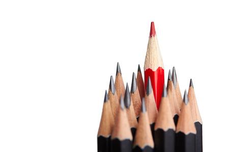 Foto de Red pencil standing out from crowd of plenty identical black fellows on white background.  - Imagen libre de derechos