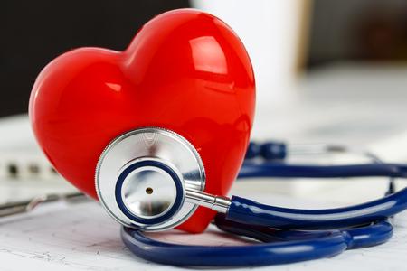 Foto de Medical stethoscope head and red toy heart lying on cardiogram chart closeup. - Imagen libre de derechos