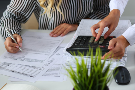 Photo pour Two female accountants counting on calculator income for tax form completion hands closeup. Internal Revenue Service inspector checking financial document. Planning budget, audit concept - image libre de droit