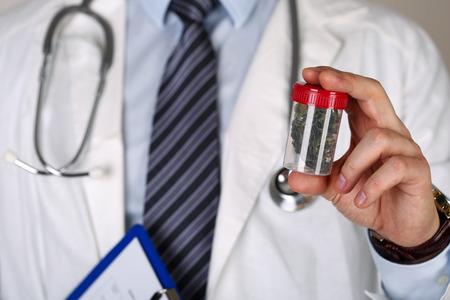 Foto de Male medicine doctor hand holding and offering to patient medical marijuana in jar. - Imagen libre de derechos