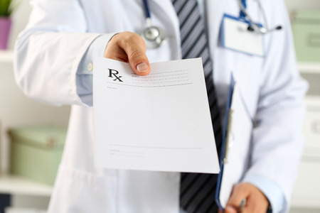 Foto de Male medicine doctor hand hold clipboard pad and give prescription to patient closeup. Panacea and life save, prescribe treatment, legal drug store, contraception concept. Empty form ready to be used - Imagen libre de derechos
