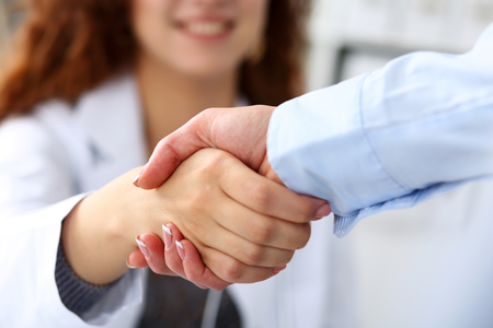 Foto de Female medicine doctor shake hand as hello with businesswoman in office closeup. Welcoming friend, introduction or thanks gesture. Tests advertisement concept. Physician ready to examine patient - Imagen libre de derechos