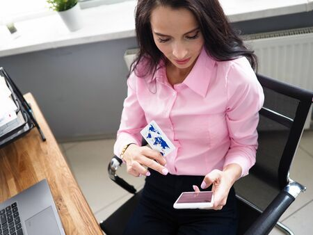 Photo pour Girl holds contactless payment card and phone. Acquiring agreement directly with bank. Cashback card, percentage purchase is returned to account. Download reports online. Order goods and services - image libre de droit