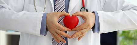 Foto de Male medicine doctor hands holding and covering red toy heart closeup. Cardio therapeutist student education physician make cardiac physical heart rate measure arrhythmia concept - Imagen libre de derechos