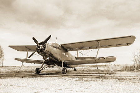 Photo pour Old airplane on field in sepia tone - image libre de droit
