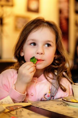 Foto de Adorable little girl with dreamy eyes sitting at cafe - Imagen libre de derechos