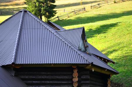 Foto de The roof is made of gray embossed metal sheets. Wooden house in the summer field - Imagen libre de derechos