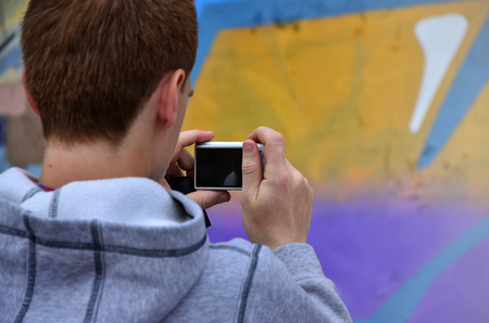 Foto de A young graffiti artist photographs his completed picture on the wall. The guy uses modern technology to capture a colorful abstract graffiti drawing. Focus on the photographing device - Imagen libre de derechos