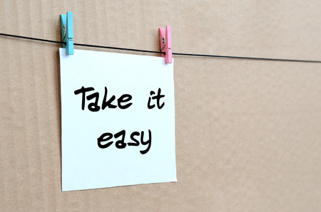 Photo pour Take it easy. Note is written on a white sticker that hangs with a clothespin on a rope on a background of brown cardboard - image libre de droit