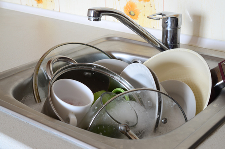 Photo pour Dirty dishes and unwashed kitchen appliances filled the kitchen sink - image libre de droit