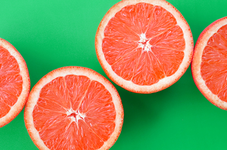 Photo pour Top view of a several grapefruit slices on bright background in green color. A saturated citrus texture image - image libre de droit