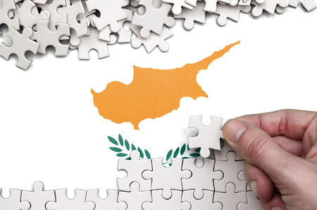 Foto de Cyprus flag  is depicted on a table on which the human hand folds a puzzle of white color. - Imagen libre de derechos