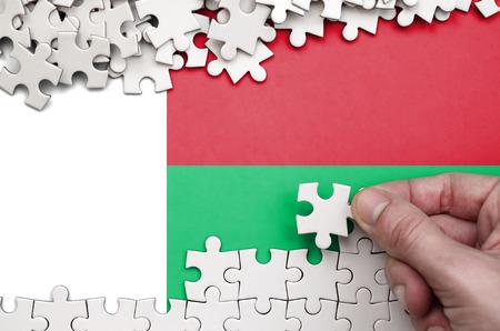 Foto de Madagascar flag  is depicted on a table on which the human hand folds a puzzle of white color. - Imagen libre de derechos