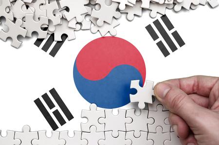 Foto de South Korea flag  is depicted on a table on which the human hand folds a puzzle of white color. - Imagen libre de derechos