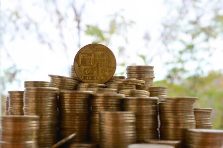 Photo pour Big amount of bitcoin stacks on blurred green trees background close up. Cryptocurrency trading concept - image libre de droit