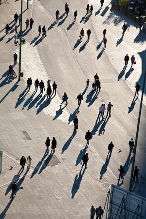 people walking in a pedestrian area seen from birds view, looking antlike