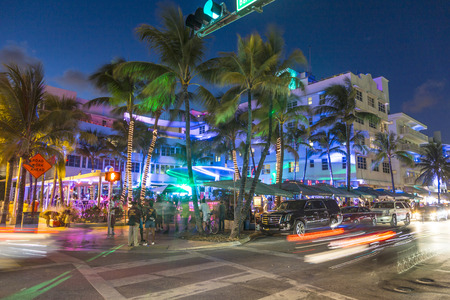 Photo for MIAMI, USA - AUG 23, 2014: Palm trees and art deco hotels at Ocean Drive by night. The road is the main thoroughfare through South Beach in Miami, USA. - Royalty Free Image