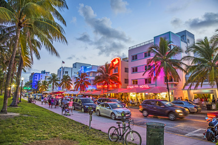 Photo pour MIAMI, USA - AUG 23, 2014: people enjoy Palm trees and art deco hotels at Ocean Drive by night. The road is the main thoroughfare through South Beach in Miami, USA. - image libre de droit