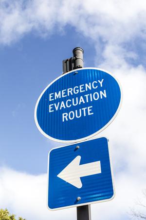 Foto de Sign emergency evacuation route in blue under blue sky - Imagen libre de derechos