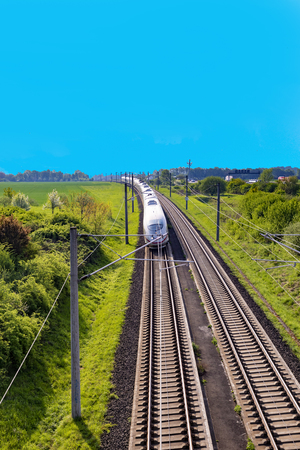 Foto per RAUNHEIM, GERMANY - APR 21, 2018: german high speed train Intercity Express (ICE) train of Deutsche Bahn passes rural landscape near Raunheim. ICE 3 class train is manufactured by Siemens. - Immagine Royalty Free