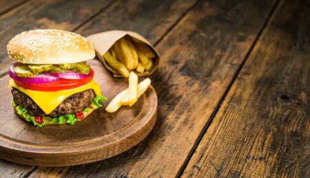 Foto per Cheese burger and french fries against wooden background. Tasty fast food. - Immagine Royalty Free