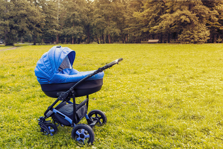 Photo for A stroller strolls in the park against the background of green trees. toned photo - Royalty Free Image