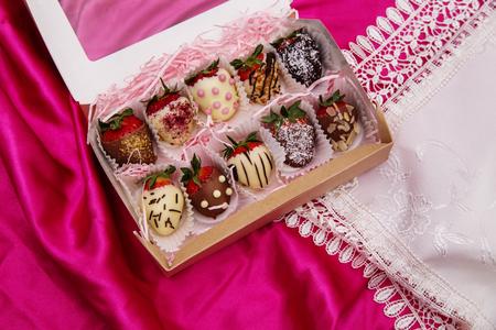 Foto de Strawberries in white and milk chocolate on a pink silk background - Imagen libre de derechos
