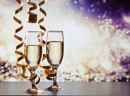 Foto de two champagne glasses with ribbons against holiday lights and fireworks - New Year celebrations - Imagen libre de derechos