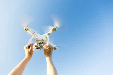 Foto de quadcopter outdoors, aerial imagery and recreation concept - closeup on human hands grip on frame of white quadrocopter flying on background of blue cloudless sky, male man caught flying drone - Imagen libre de derechos