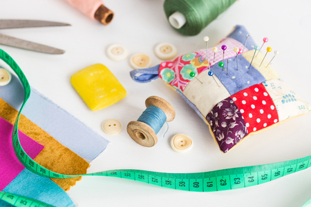 Foto de closeup sewing tools , patchwork, tailoring and fashion concept - working environment on a white table, thread spools, buttons, meter, pincushion, scissors, pieces of colored patchwork fabric, soap - Imagen libre de derechos