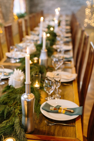 Photo pour wedding decor, interior, illumination concept. close up of served holiday table with candles in original holders that looks like bottles, among them there are fresh branches of conifer trees - image libre de droit