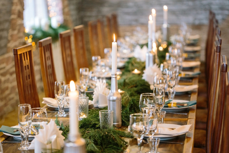 Foto de nature, winter, table setting concept. among clean plates, sparkling glasses, candle holders and other silverware there is lots of fresh and aromatic branches of some fur tree - Imagen libre de derechos