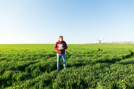 Photo for quadcopter outdoors, aerial imagery and recreation concept - male man in jeans and fleece hoodie controls the flight altitude of superb white drone, background of blue sky and field of green grass. - Royalty Free Image