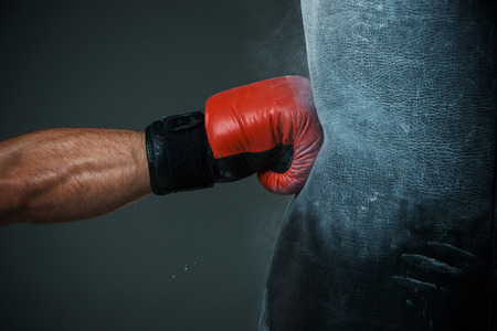 Foto de Hand  of boxer and punching bag over black background - Imagen libre de derechos