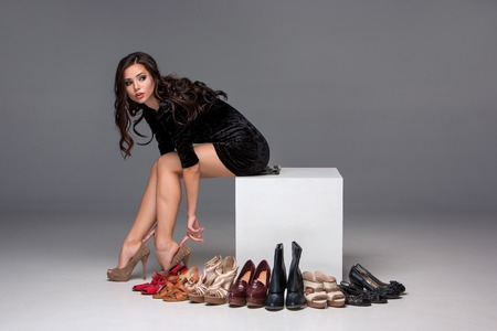 Foto de picture of sitting young attractive girl trying on high heeled shoes on a gray background - Imagen libre de derechos