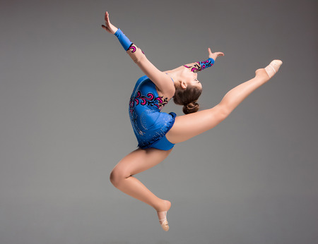 Photo pour teenager doing gymnastics dance  in  jumping on a gray background - image libre de droit