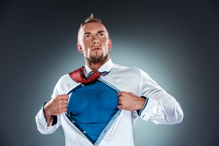 Photo pour businessman acting like a super hero and tearing his shirt off on a gray background - image libre de droit