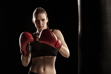 Foto de beautiful woman with the red gloves is boxing on black background - Imagen libre de derechos