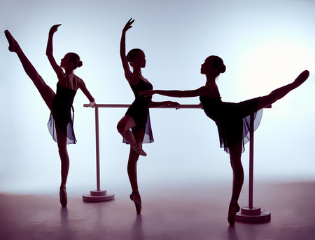 Photo for Three young ballerinas stretching on the bar on lilac background - Royalty Free Image