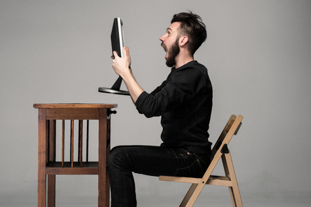 Photo pour Funny and crazy man using a computer on gray background holding a monitor - image libre de droit