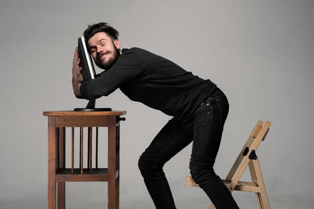 Foto de Funny and crazy man using a computer on gray background - Imagen libre de derechos