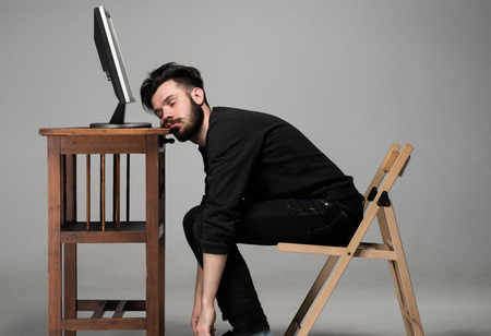 Photo pour Businessman sleeping near monitor of computer on gray background - image libre de droit