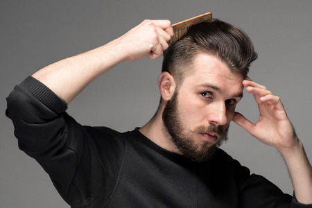 Foto de young man comb his hair on gray background - Imagen libre de derechos