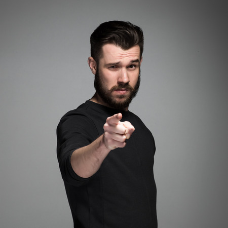 Photo pour Young man with beard and mustaches, finger pointing towards the camera on a gray background - image libre de droit