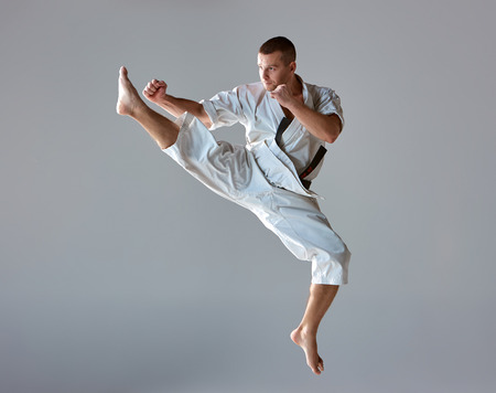 Photo for Man in white kimono and black belt training karate over gray background. - Royalty Free Image