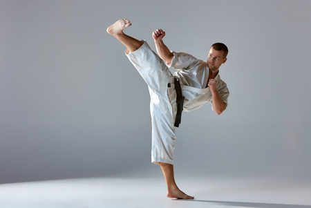Man in white kimono and black belt training karate over gray background.