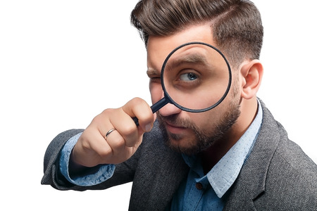 Foto de Man in a jacket with magnifying glass isolated on white background - Imagen libre de derechos