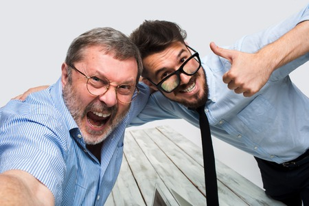 Foto de Two smiling colleagues taking the picture to them self sitting in the office, happy friends with glasses taking selfie with telephone camera  on white background - Imagen libre de derechos